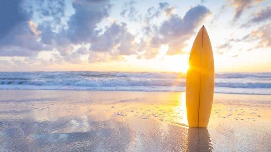 Surfboard on the beach at sunset