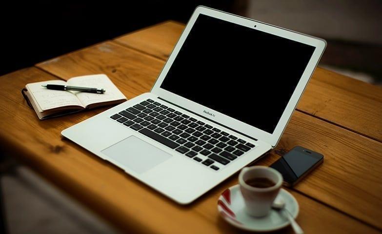 mesa com notebook e café