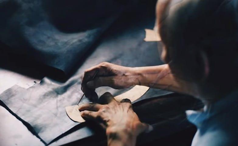 Um senhor reformando uma roupa