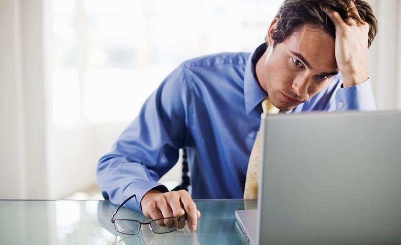 Homem frustrado no trabalho em frente ao computador
