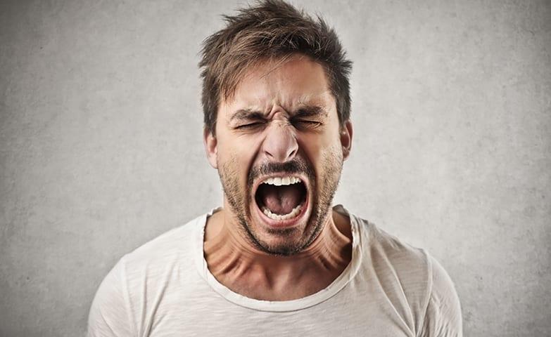 Homem com raiva e sofrendo uma crise de estresse