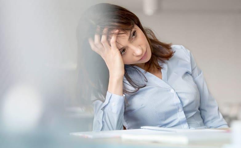 Mulher com semblante de tristeza no trabalho