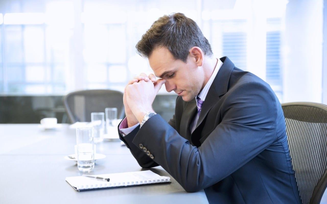 Homem começando a sentir os sintomas de depressão no trabalho