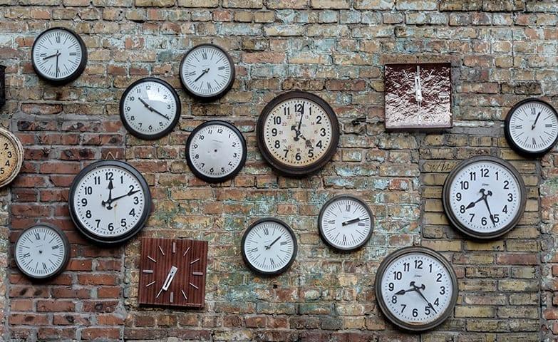 Vários relógios espalhados na parede simbolizando a correria do dia a dia